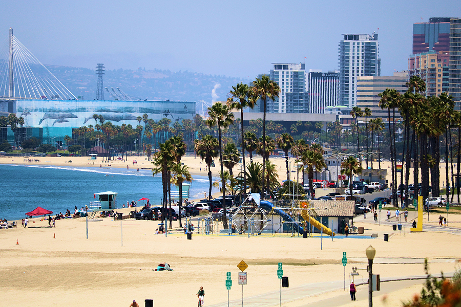 June 6, 2021 in Long Beach, CA:  People on a sandy beach besides the Pacific Ocean and the downtown skyline taken in Long Beach, CA where the public can relax on the beach and swim in the ocean next to the downtown district